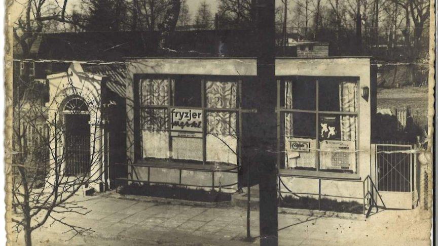 """zdjęcie z lat 60-tych XX w prezentujące  tłuszczański salon piękności dla mężczyzn i jednocześnie siedzibę """"Totolotka"""" przy ul. Powstańców."""